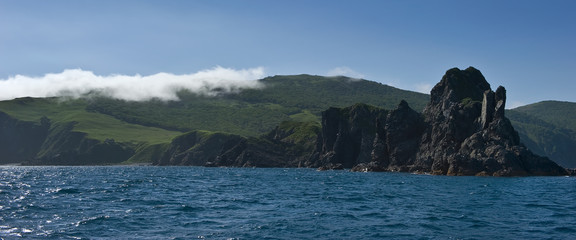 The rocky coast of the island, which covers the fog.