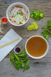 Pho Fast Food To Go on Wood Background with Peppers and Basil