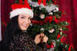 Woman with santa hat decorates tree