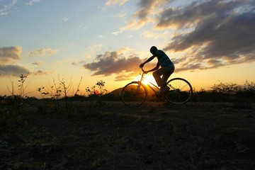 A man riding a bicycle in the evening.