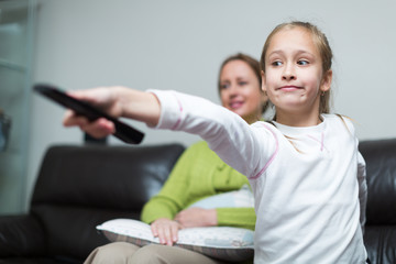 woman sitting on couch and girl holding remote control