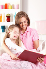 Happy mother reading book with child