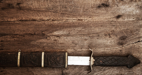 Broad sword on wooden background