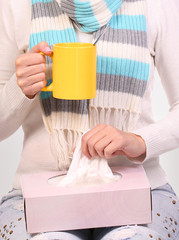 Flu cold. Sick woman with cup of tea and tissue box. Closeup