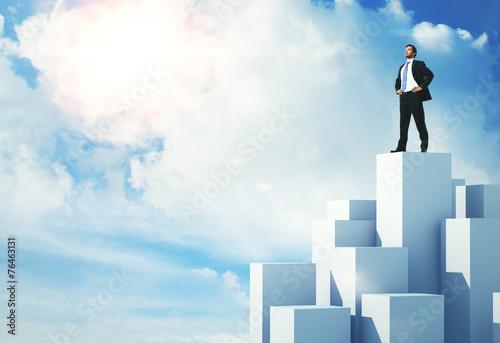 Leinwanddruck Bild Businessman standing on highest cube