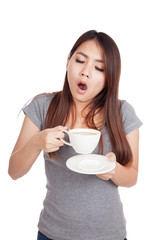 Sleepy young Asian woman yawn with cup of coffee