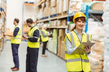 Smiling warehouse manager holding clipboard