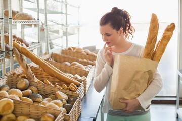 Pretty brunette holding bag of bread