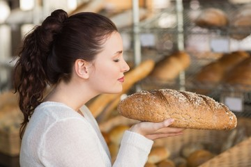Pretty brunette smelling loaf of bread
