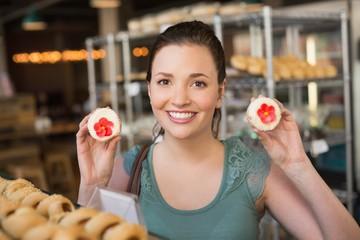 Pretty brunette showing a cupcake