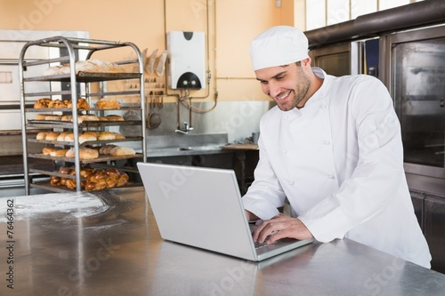 Staande foto Boord Smiling baker using laptop on worktop