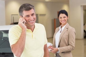 Smiling customer calling with his mobile phone