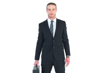 Serious businessman standing and holding briefcase