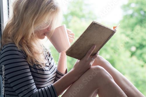 Woman sitting and enjoying book reading - 76465709