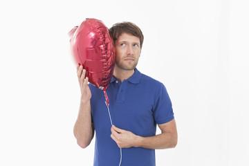 Mann mit herzförmigenn Ballon
