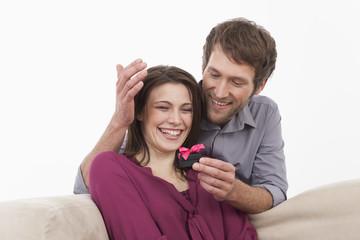 Mann überreicht Frau lächelnd ein Geschenk