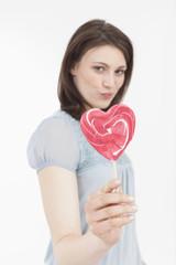 Junge Frau mit herzförmigem Lutscher