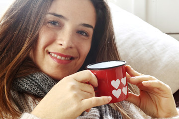 smiling girl over sofa drinking something from Valentine heart p