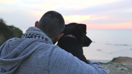 Man and dog watch the sunset
