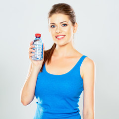 portrait of athletic woman with bottle of water posing inn stud