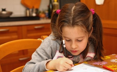 beautiful little girl writes with pencil on notebook exercises