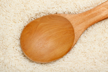 Wooden spoon on Thai fragrant jasmine rice