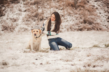Cheerful girl wears a winter hat on the dog. Holiday