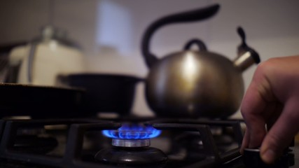 Turning on and off flame on gas stove.