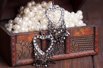 vintage earrings in a form of hearts hanging on old treasure che