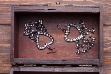vintage earrings in a form of hearts inside old treasure chest