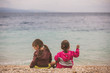 Back view of two little girls sitting near the sea