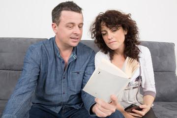 Homme et femme sur le canapé discutant autour d'un livre