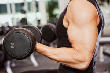 Gym: Muscular Man Works Out With Dumbells In Gym