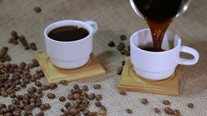 cup of steaming hot coffee with coffee beans