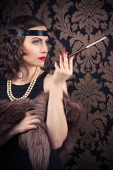 beautiful retro woman holding mouthpiece against vintage wallpap