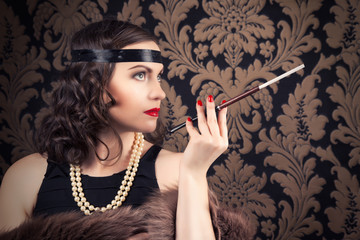 beautiful retro woman holding mouthpiece against vintage wallpap