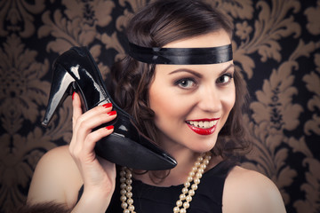 beautiful retro woman holding a black shoe like phone receiver a
