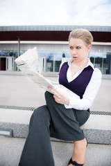 young business woman with newspaper in public