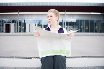 young business woman reading the stocks in public