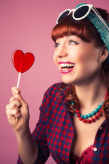 beautiful pin-up girl posing with red heart-shaped lollipop agai