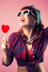 beautiful pin-up girl posing with red heart-shaped lollipop agai