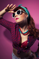 beautiful pin-up girl posing with white sunglasses against pink