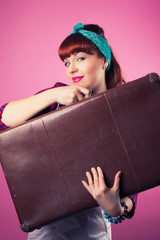 beautiful pin-up girl posing with vintage suitcase against pink