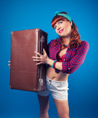 beautiful pin-up girl posing with vintage suitcase against blue