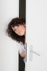 Femme passant sa tête derrière la porte
