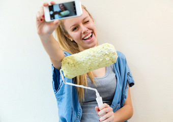 Young beautiful woman painting hew new home. Selfie concept.