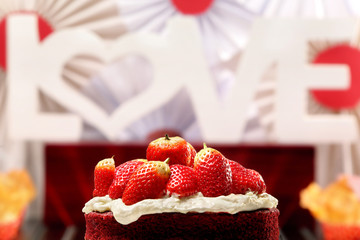 Red velvet cake with strawberries and inscription love in the ba