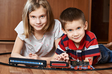Sister and brother playing with railway