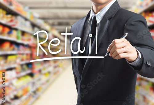 Leinwanddruck Bild Business man writing word retail in the supermarket
