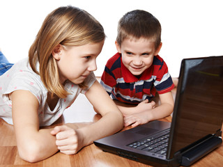 Sister and brother looking to laptop